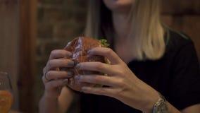 Zamyka w górę materiału filmowego młoda kobieta je hamburger Portret pcha puszek trzyma w rękach młoda kobieta hamburger, zbiory wideo