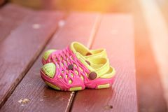Zamyka w górę menchii i zielenieje dziecka ` s sandałów buty na stole zdjęcia royalty free