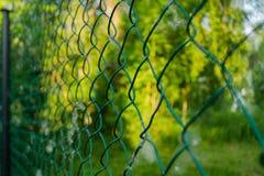 Zamyka w górę metalu połączenia w ogródzie Diamentowej siatki druciany ogrodzenie na zamazanym zielonym tle Żelazna greting sieć  zdjęcie stock