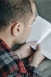 Zamyka w górę modnisia mężczyzna w czerwonej w kratkę koszulowej czytelniczej książce i kłamstwie Obrazy Stock