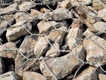 Zamyka w górę naturalnych kamieni wewnątrz utrzymuje drucianą siatkę fotografia stock