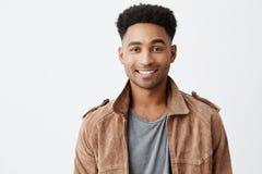 Zamyka w górę odosobnionego portreta młody ciemnoskóry atrakcyjny facet z afro fryzurą w popielatej koszulce pod brown kurtką zdjęcie stock