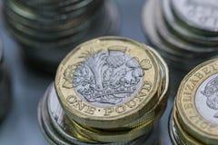 Zamyka w górę ostrość fotografii nowego Zlanego królestwa Funtowa moneta wśród innych Brytyjskich monet, Obrazy Royalty Free