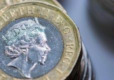 Zamyka w górę ostrość fotografii nowego Zlanego królestwa Funtowa moneta wśród innych Brytyjskich monet, Obrazy Stock