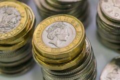 Zamyka w górę ostrość fotografii nowego Zlanego królestwa Funtowa moneta wśród innych Brytyjskich monet, Obraz Stock