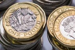 Zamyka w górę ostrość fotografii nowego Zlanego królestwa Funtowa moneta wśród innych Brytyjskich monet, Zdjęcie Royalty Free