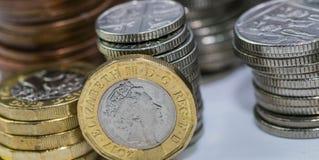 Zamyka w górę ostrość fotografii nowego Zlanego królestwa Funtowa moneta wśród innych Brytyjskich monet, Zdjęcia Stock