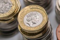Zamyka w górę ostrość fotografii nowego Zlanego królestwa Funtowa moneta wśród innych Brytyjskich monet, Zdjęcie Stock