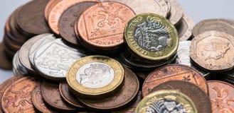 Zamyka w górę ostrość fotografii nowego Zlanego królestwa Funtowa moneta wśród innych Brytyjskich monet, Obraz Royalty Free