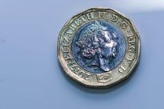 Zamyka w górę ostrość fotografii nowego Zlanego królestwa Funtowa moneta wśród innych Brytyjskich monet, Fotografia Stock