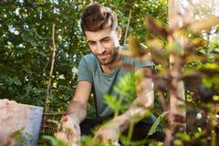 Zamyka w górę outdoors portreta szczęśliwy dojrzały brodaty caucasian mężczyzna ono uśmiecha się, pracuje w ogrodowym pobliskim w zdjęcia stock