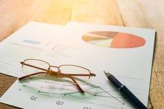 Zamyka w górę pióra z zbiorczym raportem na stołowym biurze i eyeglasses Zdjęcia Stock