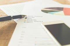 Zamyka w górę pióra z zbiorczym raportem na stołowym biurze i smartphone Obraz Stock