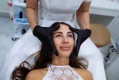 Zamyka w górę pięknych żeńskich twarzy i cosmetologist ` s ręk Botox chuje, hyalurowego kwasu zastrzyk Odmładzanie i fotografia royalty free