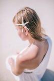 Zamyka w górę plenerowego twarzowego portreta młody blondynka modela obsiadanie na białej piasek plaży z białą rozgwiazdą w włosy zdjęcia stock
