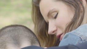 Zamyka w górę portreta ślicznego macierzystego uściśnięcia młodego syna i całuje on Matki opieka i miłość zdjęcie wideo