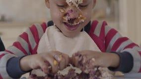 Zamyka w górę portreta afroamerykańska chłopiec błocąca w torcie i ugniatać kawałek torta lying on the beach w talerzu na zbiory wideo
