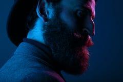 Zamyka w górę portreta brodaty mężczyzna w eleganckim kapeluszu i kostiumu, pozuje w profilu w studiu, odizolowywającym na błękit zdjęcia royalty free