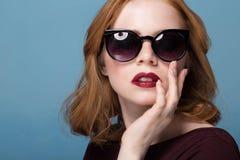 Zamyka w górę portreta elegancka młoda kobieta w okularach przeciwsłonecznych przeciw błękitnemu tłu Moda, splendor, moda Fotografia Royalty Free