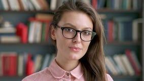 Zamyka w górę portreta młoda ładna bibliotekarska kobieta uśmiecha się szczęśliwą patrzeje kamerę w bibliotecznym półki na książk zbiory