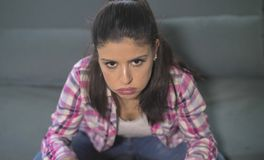 Zamyka w górę portreta młoda atrakcyjna, smutna latynoska kobieta siedzi w domu leżankę patrzeje i zdjęcie stock
