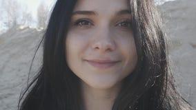 Zamyka w górę portreta młoda brunetki kobieta plenerowa na piaska tle zbiory