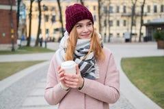 Zamyka w górę portreta młoda elegancka blondynki dziewczyna w czerwonego kapeluszowego mienia takeout filiżance zdjęcie royalty free
