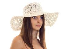 Zamyka w górę portreta młoda piękna brunetki dziewczyna w słomianym kapeluszu z szeroki ronda pozować odizolowywam na białym tle Obrazy Royalty Free