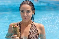 Zamyka w górę portreta mokra Europejska brunetki młodej damy pozycja w basenie, patrzejący bezpośrednio przy kamerą, trzyma kokta obrazy stock