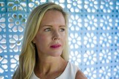 Zamyka w górę portreta piękna i zrelaksowana Kaukaska blond kobieta patrzeje daleko od na błękitnym deseniowym tle z niebieskimi  obraz royalty free