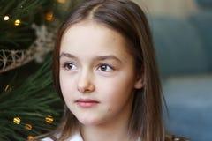 Zamyka w górę portreta piękna mała dziewczynka siedzi pod choinki rojeniem z brown oczami fotografia stock
