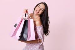 Zamyka w górę portreta piękna uśmiechnięta kobieta z długim ciemnym włosy, ubierającą polki kropki suknią, chwyt torbami na zakup obraz stock