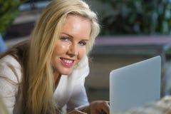 Zamyka w górę portreta pięknego i szczęśliwej blond kobiety 40s relaksującej w domu używać internet na laptopu pracujący łgarski  obrazy stock