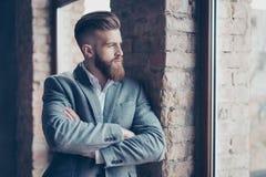 Zamyka w górę portreta przystojny brodaty młody człowiek w kostiumu opierać obraz stock