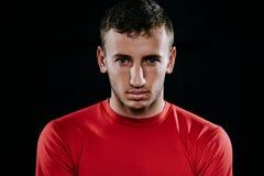 Zamyka w górę portreta przystojny Kaukaski sportowiec jest ubranym czerwonego sportswear i pozuje po ćwiczeń na ciemnym tle Zdrow Zdjęcie Stock