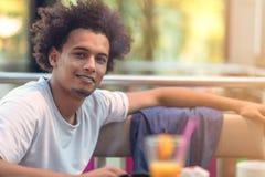 Zamyka w górę portreta przystojny rozochocony afrykański mężczyzna ono uśmiecha się patrzejący kamerę zdjęcie stock