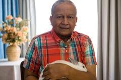 Zamyka w górę portreta starszego mężczyzna mienia królik przy emerytura domem obrazy stock