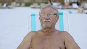 Zamyka w górę portreta starszy mężczyzna patrzeje kamera przy plażą w deckchair 4k z wąsem zbiory wideo