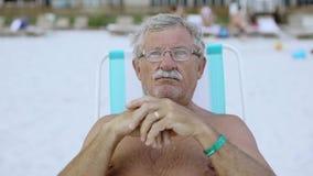 Zamyka w górę portreta starszy mężczyzna patrzeje kamera przy plażą w deckchair 4k z wąsem zdjęcie wideo