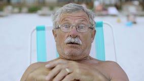 Zamyka w górę portreta starszy mężczyzna patrzeje kamera przy plażą w deckchair 4k z wąsem zbiory