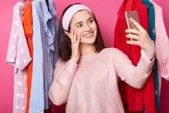 Zamyka w górę portreta szczęśliwa kobieta z smartphone robi selfie przy sklepem odzieżowym, utrzymanie ręka na policzku, ko fotografia royalty free