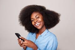 Zamyka w górę portreta szczęśliwa młoda amerykanin afrykańskiego pochodzenia kobieta ono uśmiecha się z telefonem komórkowym zdjęcie royalty free