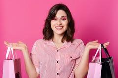Zamyka w górę portreta szczęśliwa piękna uśmiechnięta brunetki kobieta z falistym włosy, ubierająca pasiasta koszula, chwyt torby obraz stock