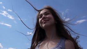 Zamyka w górę portreta uśmiechnięta piękna młoda dziewczyna na niebieskiego nieba tle z podmuchowym włosy w wiatrze zbiory wideo