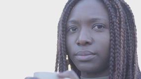 Zamyka w górę portreta ufnego amerykanin afrykańskiego pochodzenia młoda czarna uśmiechnięta kobieta z gorącym filiżanka kawy na  zbiory wideo