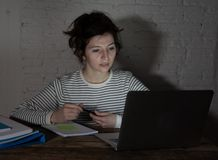 Zamyka w górę portreta zapracowana i zmęczona młoda kobieta studiuje póżno przy nocą na markotnym świetle obrazy stock