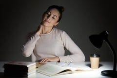 Zamyka w górę portreta zmęczona studencka kobieta z szyja bólem na ciemnym tle, siedzi pod światłem lampa, przygotowywa dla, obraz stock