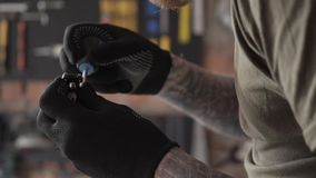 Zamyka w górę profilu dorosły brodaty elektryk pracuje z szczegółami stoi przy stołem w garażu Mężczyzna pracuje w a zdjęcie wideo
