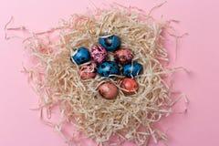 Zamyka w górę przepiórki Easter jajek w gniazdeczku przy różowym tłem obrazy stock