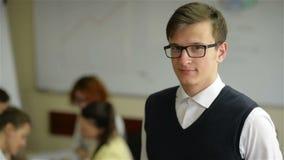Zamyka w górę przystojnego młodego pracownika jest ubranym eyeglasses i flanelową koszula w małym biurze z innym personelem w tle zbiory